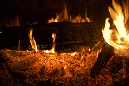 Close up of campfire at night showing logs, flames and burning embers. Banco de Imagens