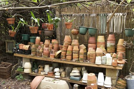 A large assortment of numerous types of flower pots staked up and hanging outdoors in tropical setting.