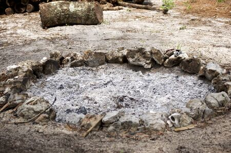 A stone circle fire pit filled with ash from recent fire.