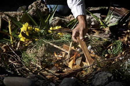 A mayan priest is lighting fire with candles and wood in ceremonial fire ritual, flowers and herbs can be seen. Banco de Imagens