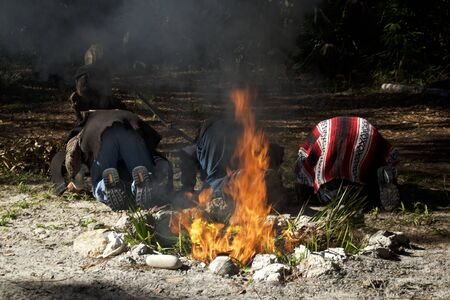 Three mayan priests are bowing in prayer with backs to ceremonial fire during ritual.