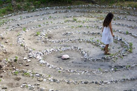 A young woman with long brown hair and white dress is walking away from the center of a maze or stone labyrinth. Banco de Imagens