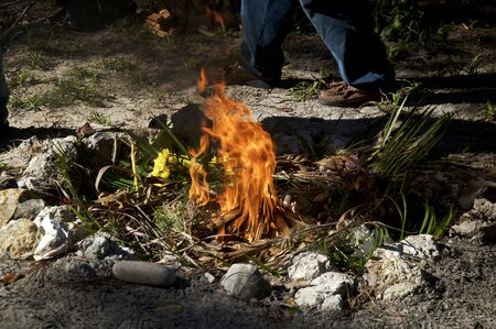 a stone fire pit with flames burning the ritual offerings during a mayan religious ceremony outdoors.