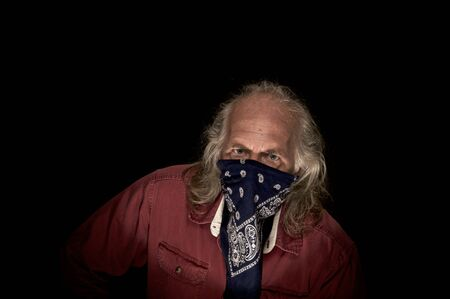 Un bandido enmascarado de pelo largo con un pañuelo azul para cubrir la cara y una camisa roja mirando fijamente al espectador con fondo oscuro.