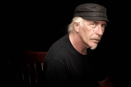 An older white biker male sitting in a dark room wearing black t shirt and leather cap, looking serious at viewer, three quarter view portrait. Stock Photo