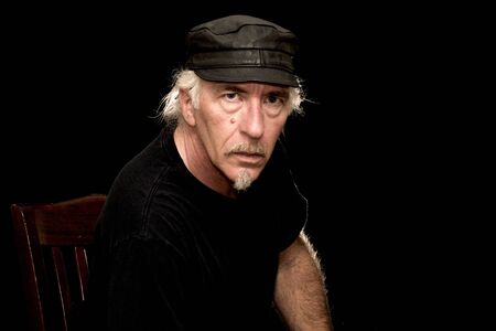 An older white biker male sitting in a dark room wearing black t shirt and leather cap, looking serious at viewer. Stock Photo