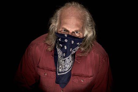 Un bandido enmascarado de pelo largo con un pañuelo azul para cubrir la cara y una camisa roja mirando al espectador con un fondo oscuro.