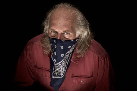 A long haired masked man wearing a blue bandana to cover the face and a red shirt , hunched over and looking intently at viewer with dark background.