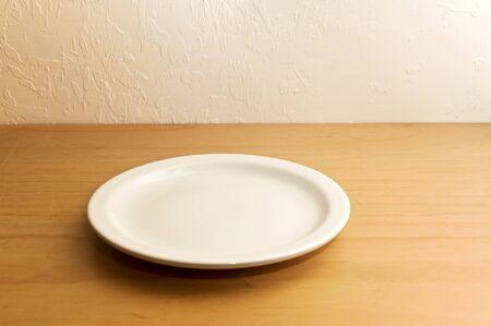 Stary drewniany licznik na stiukowej ścianie z pustym białym talerzem lub naczyniem.