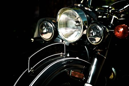 Front end of vintage black sidecar motorcycle, showing headlights and blank front fender license plate, high contrast.