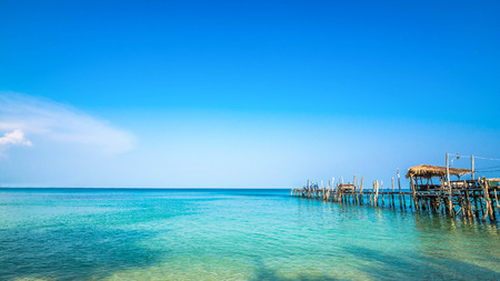 Old wooden pier in Clear water and beautiful bay on Samet Island, Rayong, Thailand.
