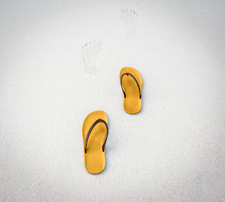 Footprints and brown shoes on White Sand Beach.
