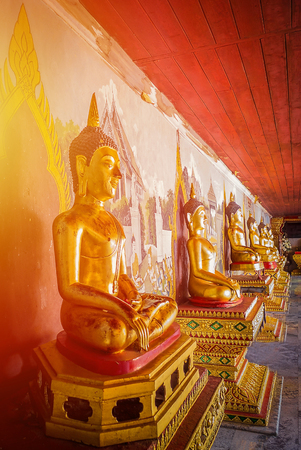 The elegance of the Golden Buddha statue with Orange light. Banco de Imagens