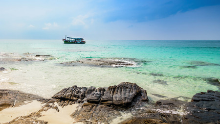 Floating boat near the rocky shore in bay of Samet Island, Rayong, Thailand.