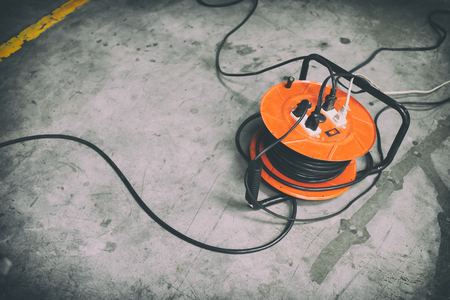 Cable reel Orange color Be plugged with Black Cable Wire Placed on the floor. Stok Fotoğraf