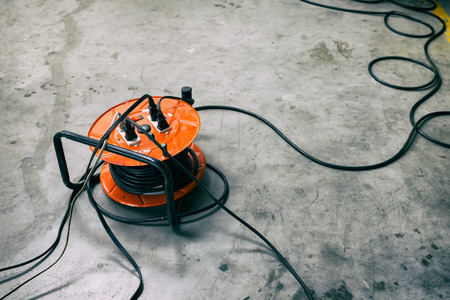 Cable reel Orange color Be plugged with Black Cable Wire Placed on the floor. Archivio Fotografico