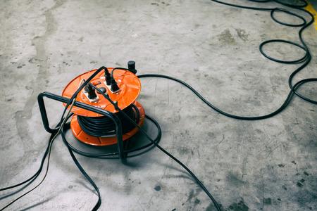 Kabeltrommel Orange Farbe Mit schwarzem Kabeldraht auf dem Boden verstopfen.