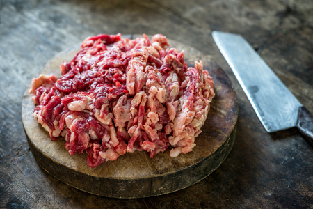 Shredded Raw beef on the cutting board with knife. Reklamní fotografie