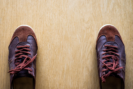 Old brown sneakers on a wooden floor top view.