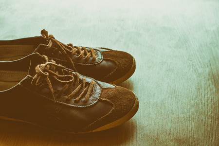 Old brown sneakers on a wooden floor, vintage color tone.