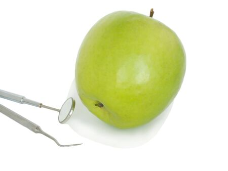 Green apple on a white background and stomatologic tools. Stock Photo