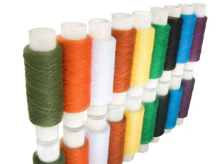 Multi-coloured a thread in spools on a white background