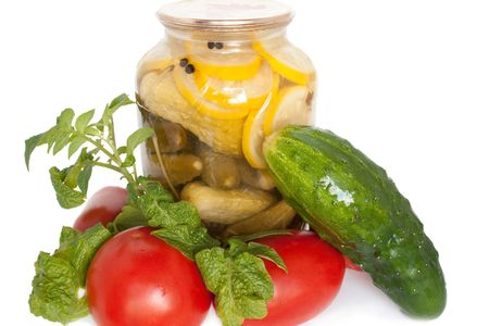 gherkins: Fresh garden vegetables and also a jarred of canned cucumbers on white background