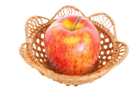 A large red apple is in a basket, on a white background