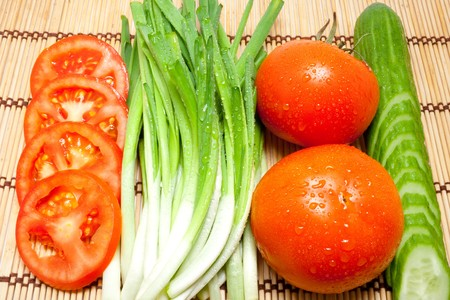 kitchen device: Fresh tomatoes, cucumbers and onions on a kitchen device