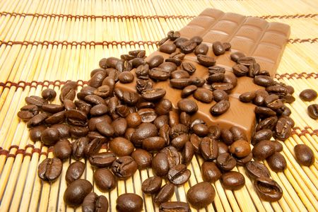 Coffee grains and stick of chocolate on a table-cloth skies Stock Photo