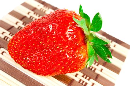 Composition on a white background. Large, ripe strawberry on a mat  photo