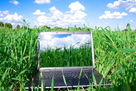 laptop computer on the green grass and blue sky Stock Photo