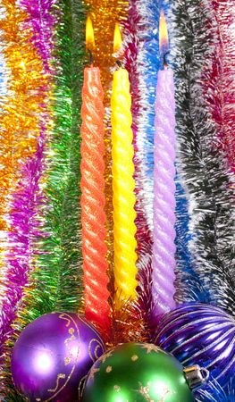 Three christmas candles and Christmas decorations on a background tinsel