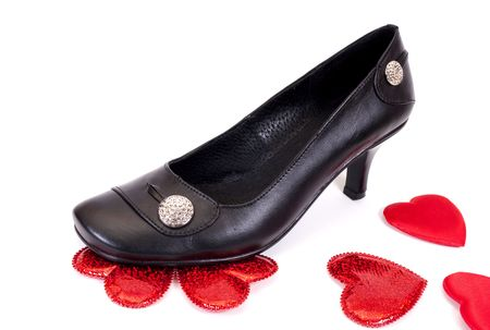 Black womanish shoes trample down romantic hearts on a white background. photo