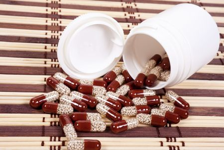 granular: Brown capsules with granular medicine on a mat background.
