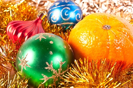 Christmas and new-year decorations. Red beautiful Christmas toy and tangerine on a tinsel background photo