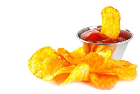 titbits: Silver sauce-boat and fried potato chips on a white background