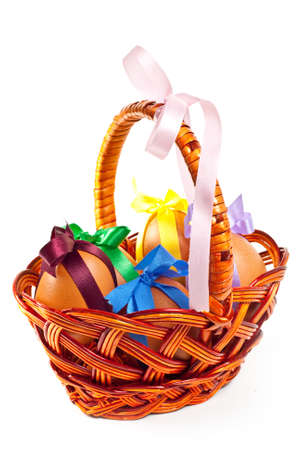 Easter eggs in brown basket on a white background  photo