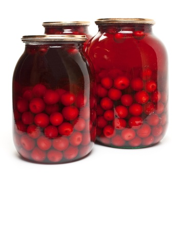 jar with preserved cherries on white background photo