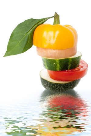 Different Sliced vegetables combined studs reflected in water on a white background  Stock Photo