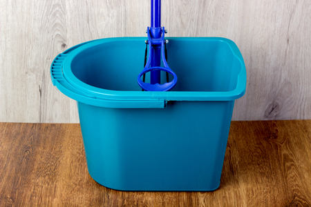 mop and blue bucket on the floor Stock Photo