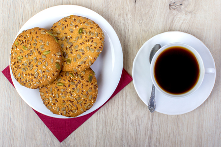 Cup of coffee wiyh pile of various shortbread and oat cookies with cereals on wooden background. Top view.
