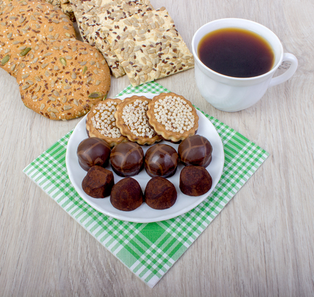 Cup of coffee and cookies on wood background