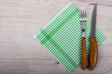 top view of fork and knife on checkered napkin