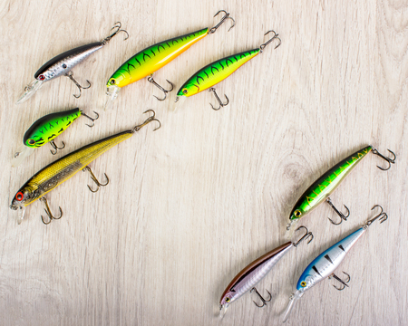 pastime: Fishing lures on a wooden background. Fishing equipment. Stock Photo