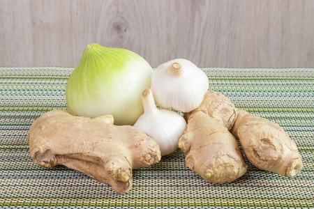onion, garlic bulb and ginger on the table Stock Photo