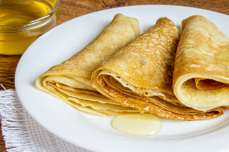 hotcakes: pancakes with honey syrup on a white plate. traditional crepe or pancake.