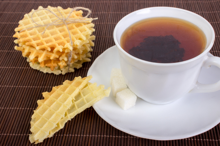 teaparty: Breakfast with Waffles, Black Cup of Tea and Pieces of Waffle on Wooden Surface.