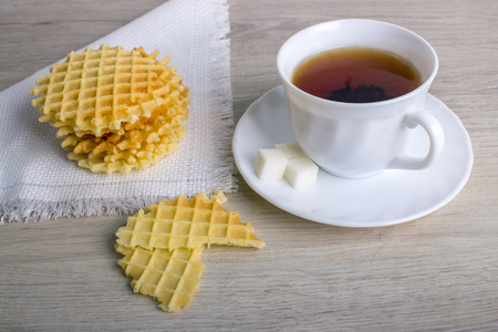 teaparty: Breakfast with white cup of black tea with waffles stack on napkin and pieces of waffle on wooden surface. Stock Photo
