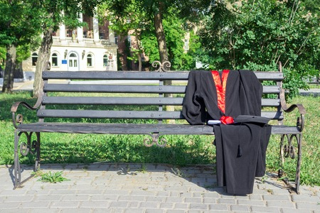 completion: Graduation cap, hat with black tassel, mantle with a degree of paper on a park bench
